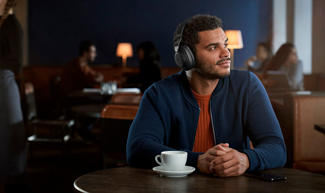 Man using Jabra Elite 85h in a cafe